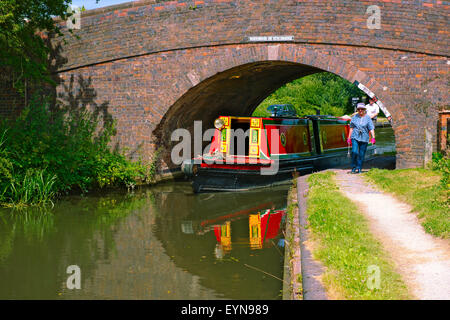 Canal narrow boat going under bridge on Birmingham and Fazeley Canal near lock 6, Sutton Coldfield West Midlands - Stock Photo