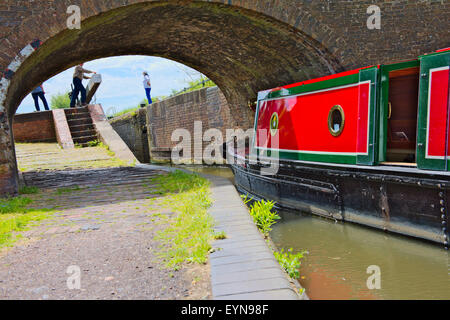 Canal narrow boat going under bridge lock 6 open on Birmingham and Fazeley Canal, Sutton Coldfield West Midlands, - Stock Photo