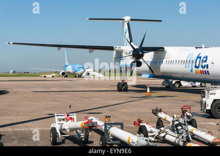 Aircraft tow bars on the apron at East Midlands Airport next to a Flybe Dash 8 turboprop aeroplane - Stock Photo
