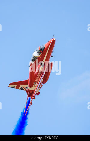 Single RAF Red Arrow passing low overhead during an airshow display - Stock Photo