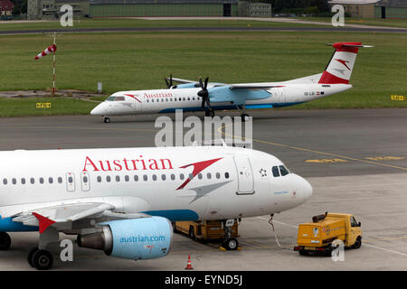 Bombardier Dash 8-Q402 and Airbus A320 Austrian on runway , Blue Danube Airport Linz - Stock Photo