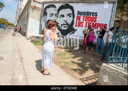 HAVANA, CUBA - JUNE, 2011: Cubans line up in front of a billboard of propaganda featuring revolutionary leaders. - Stock Photo