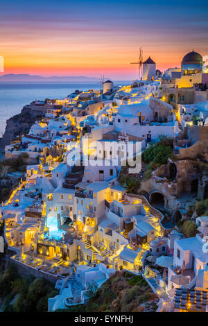 Iconic sunset in the town of Oia on the greek island Santorini (Thera). - Stock Photo