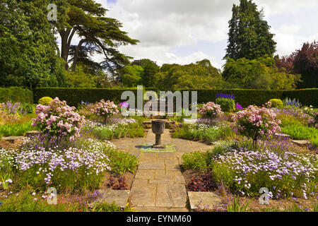 Quiet corner of a flagged English garden with stone vase. - Stock Photo