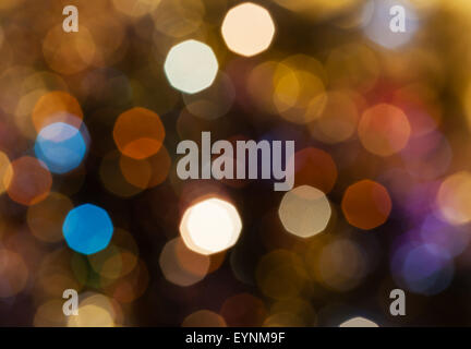 abstract blurred background - dark brown shimmering Christmas lights of electric garlands on Xmas tree - Stock Photo