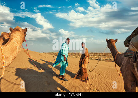 Two cameleers camel drivers with camels in dunes of Thar deser - Stock Photo