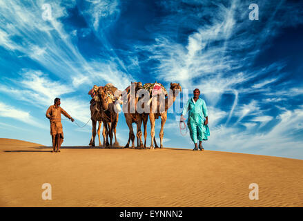 Two cameleers camel drivers with camels in dunes of Thar desert - Stock Photo