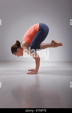 Fit yogini woman practices yoga asana  Bakasana - Stock Photo