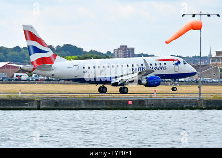 British Airways Cityflyer Embraer 170 G-LCYE plane landing at London City Airport with windsock London Docklands - Stock Photo