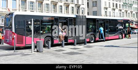 Marseilles France RTM long public transport bendy bus & passengers boarding at French bus stop adjacent Vieux Port - Stock Photo