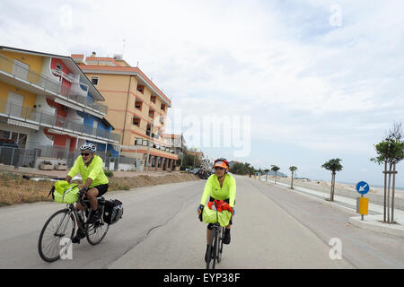 Two touring cyclists riding their bikes on a road beside the Adriatic Coast of Italy. - Stock Photo