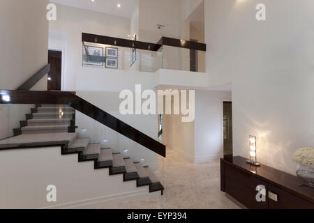 Room with a staircase in a modern house, warmed up with artworks on the walls - Stock Photo