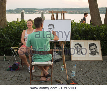 Street artist drawing a likeness of young woman in Uberlingen on the shores of Lake Constance, Germany, - Stock Photo