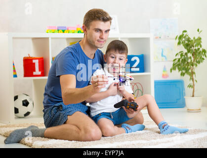 Dad and his son child play with RC helicopter toy - Stock Photo