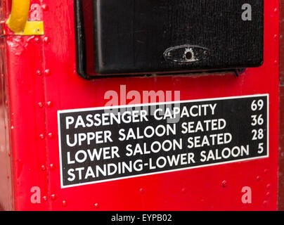 Capacity sign at entry of classic red Routemaster double-decker bus in London, England, UK - Stock Photo