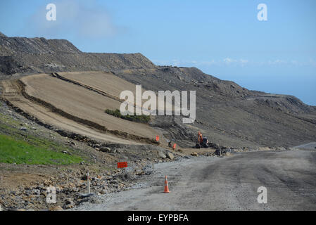 WESTPORT, NEW ZEALAND, MARCH 11, 2015: a digger prepares a man-made hillside for planting of native vegetation - Stock Photo