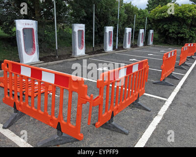 Tesla charging points being implemented on a motorway service area in the UK, with barriers around - Stock Photo