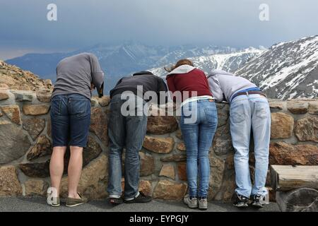 Tourists at Rocky Mountain National Park in Colorado leaning over a wall to look at something. - Stock Photo