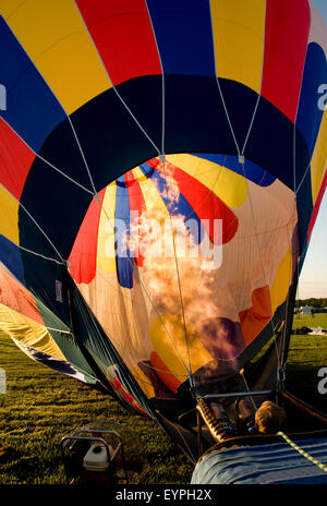 Hot air balloon being inflated in preparation for flight with flames shooting into the envelope. - Stock Photo