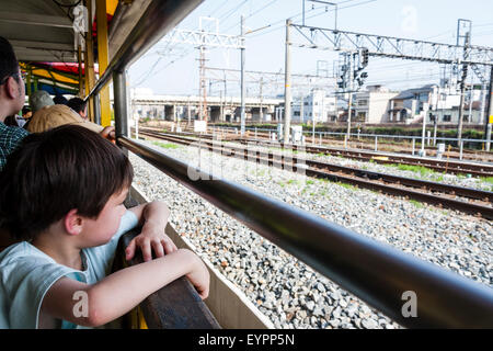 6 to 9 year old Caucasian child, boy. Looking out of open window type train as it passes other lines, other passengers - Stock Photo