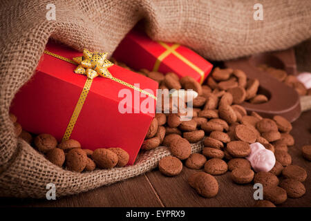 'De zak van Sinterklaas' (St. Nicholas' bag) filled with 'pepernoten', a letter of chocolate and sweets. A Dutch - Stock Photo