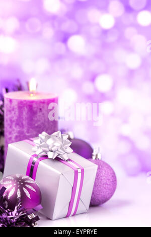 Purple and silver Christmas baubles, a gift and a candle in front of defocused purple and white lights. - Stock Photo