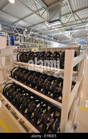 Inside a modern car factory, vehicles and parts move through the production process, steering wheels waiting to - Stock Photo