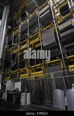 Inside a modern car factory, vehicles and parts move through the production process, racks of body parts - Stock Photo