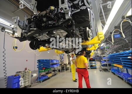 Inside a modern car factory, vehicles and parts move through the production process, working below suspended cars - Stock Photo