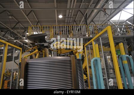 Inside a modern car factory, vehicles and parts move through the production process, stack of body panels and robot - Stock Photo