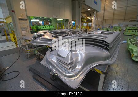 Inside a modern car factory, vehicles and parts move through the production process, freshly stamped body panels - Stock Photo