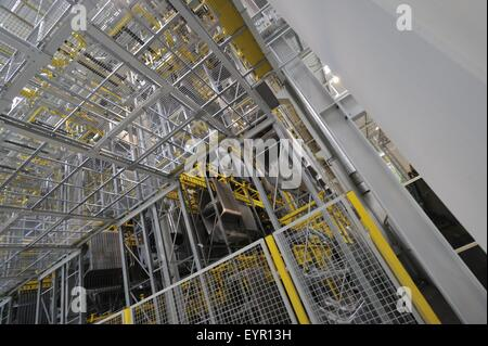 Inside a modern car factory, vehicles and parts move through the production process, huge storage area - Stock Photo