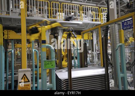 Inside a modern car factory, vehicles and parts move through the production process, robot picking body panels - Stock Photo