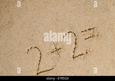 handwritten numbers on sand background - Stock Photo