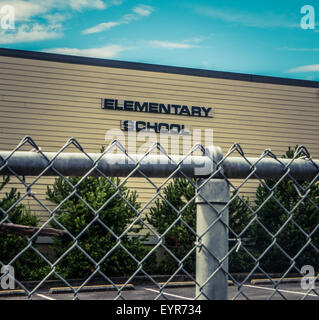 Typical USA Elementary School With Chain Link Fence In Foreground - Stock Photo