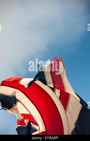 England. Ragged, tattered, torn flying Union Jack. - Stock Photo