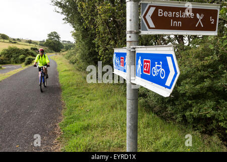 Cyclist and Cycle Route 27 Sign on the Granite Way at Lake Viaduct, Dartmoor, Devon, UK - Stock Photo