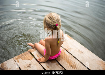 Rear view of child blond girl sitting on pier looking at view of pond with her feet in the water - Stock Photo