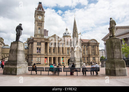 People sitting on a bench facing birmingham City Museum and Art Gallery - Stock Photo