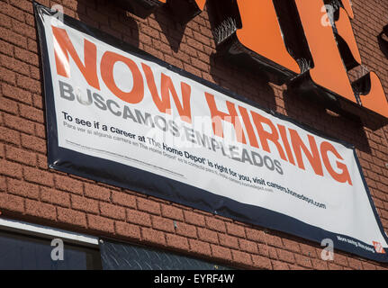 Now Hiring sign at a Home Depot - Stock Photo