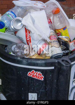 Notting Hill, London, England. Over flowing rubbish bin, with 'Art in Transit' sticker. Carnival. - Stock Photo