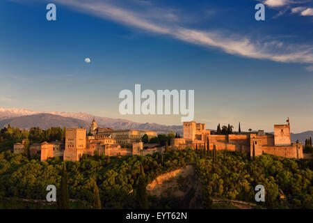 Moon and golden sunset on hilltop Alhambra Palace fortress complex Granada Spain with snow capped Sierra Nevada - Stock Photo