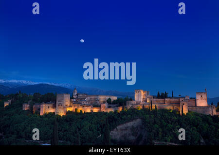 Moonrise over lit Alhambra Palace Complex Granada at twilight with Sierra Nevada Mountains Spain - Stock Photo