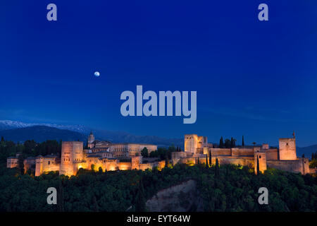 Indigo sky and moonrise over lit hilltop Alhambra Palace fortress complex at twilight Granada Spain - Stock Photo