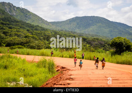 Children running on a dirt road in Angola - Stock Photo