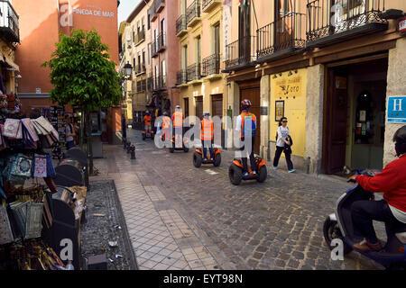 Line of bright orange Segway rider tourists on Elvira street Granada Spain - Stock Photo