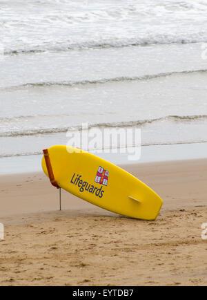RNLI Lifeguards Surfboard on Beach in England, UK - Stock Photo