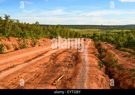 Dirt road of red mud / laterite in Angola near Chicuma - Stock Photo