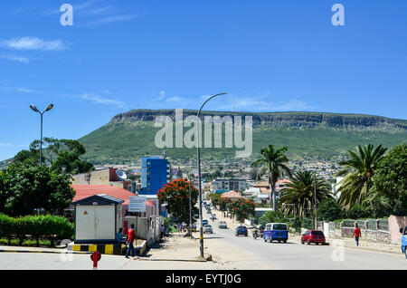 Street view of the city of Lubango, Angola, with mountain and Cristo Rei in the background - Stock Photo