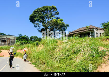 Two women carrying bags on their head on the road by an abandoned house in Angola - Stock Photo